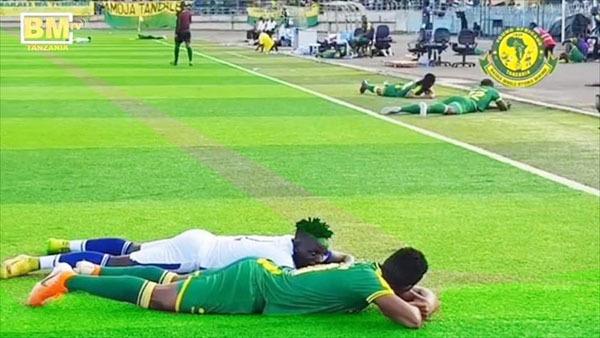 Hai cầu thủ trò chuyện trong lúcnằm xuống sân đợi ong qua.