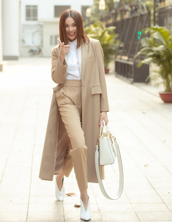 <p> Người đẹp diện phong cách thanh lịch nhưng cá tính, với sơ mi trắng, quần tây màu camel (màu lông lạc đà) và trench coat cùng tông. Cô mix thêm túi xách và giày trắng, đồng điệu với màu sơ mi. Những hành động vui nhộn của cô thu hút mọi ống kính.</p>