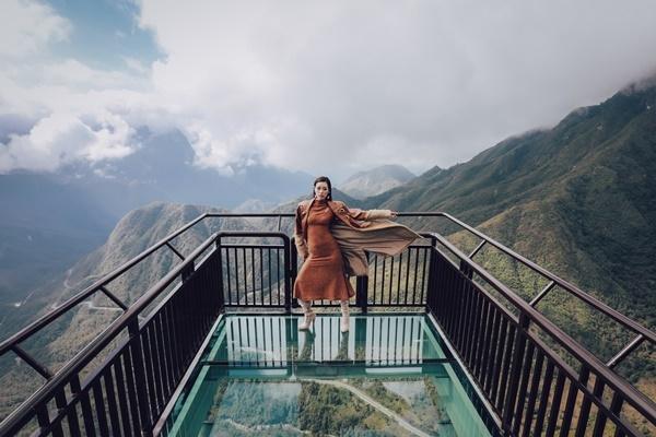 Khánh Vân mặc bộ trang phục kín cổng cao tường gam màu nâu. Cô tạo dáng ở độ cao hơn 2.000 mét so với mực nước biển.