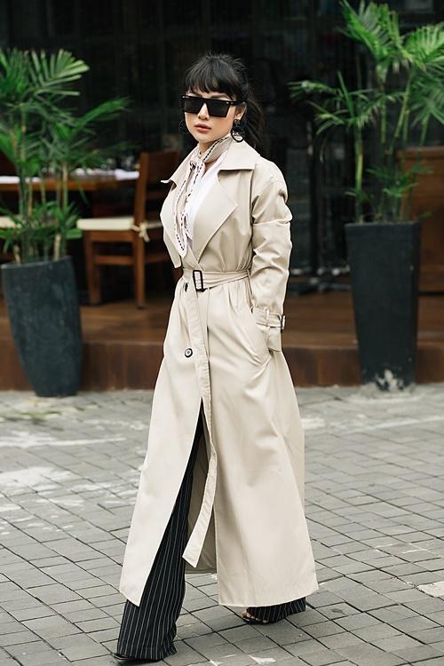 Lựa chọn áo khoác dáng dài, Thu Hiền mix cùng quần ống suông cạp cao. Phần ống suông sẽ giấu đi đôi giày cao gót gần 15 cm, tôn vóc dáng của người mặc.