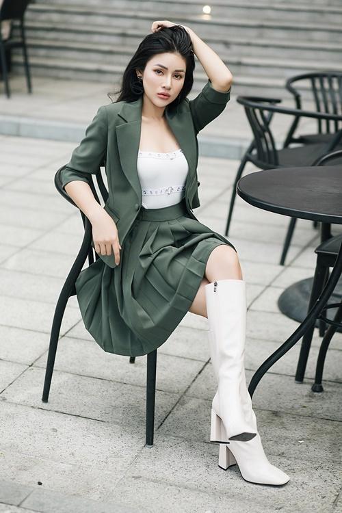 MC gốc Quảng Bình phối chân váy cùng vest tay lỡ và boots trắng gót vuông.