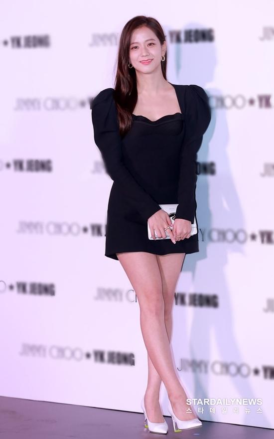 Nữ idol trang điểm tông nhẹ nhàng, diện bộ váy đen ôm sát có thiết kế tay bồng mix cùng túi xách, giày cao gót màu trắng.