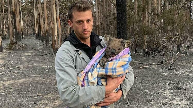 Jack Bruce ôm Wilbur, một con gấu túi, vừa được cứu thoát khỏi đám cháy. Ảnh: CNN.
