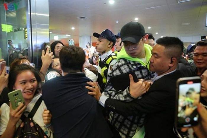 Chan Yeol (mũ đen đeo kính) vất vả di chuyển giữa vòng vây của fan.