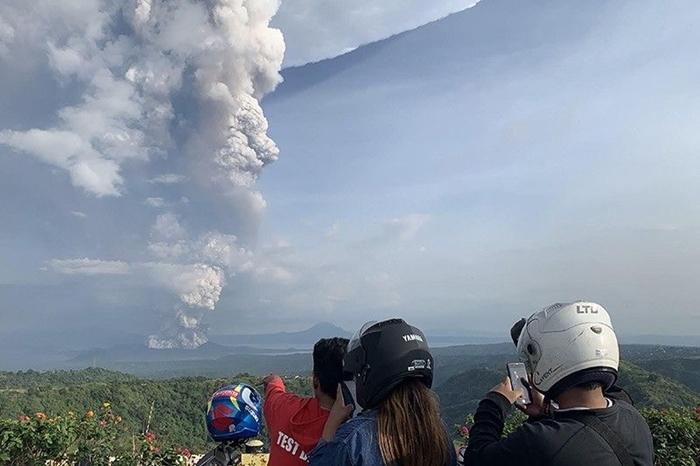 Người dânchụp ảnh vụ phun tràonúi lửa Taal khi nhìn từ thị trấn Tagaytay thuộc tỉnh Cavite, phía tây nam Manila. Ảnh: AFP.