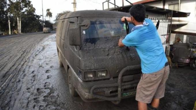 <p> Người đàn ông cố gắng lau bụi khỏi cửa kính xe ôtô ngập trong tro.</p>