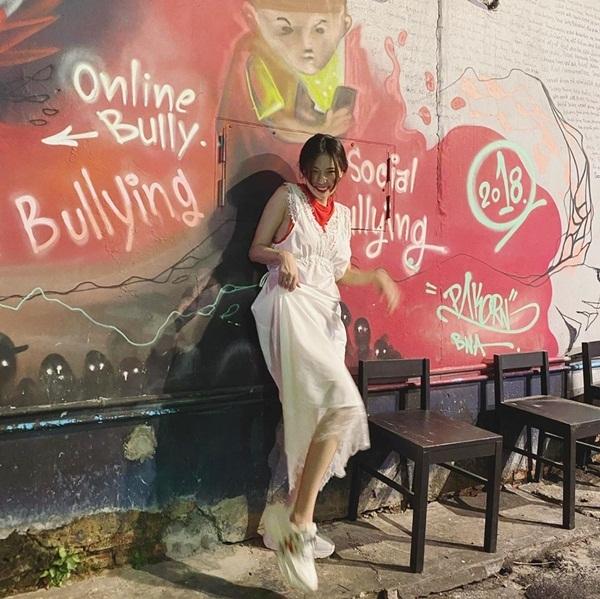 Hyuna cười thoải mái tạo dáng trước bức tường có chữ bắt nạt trên mạng.