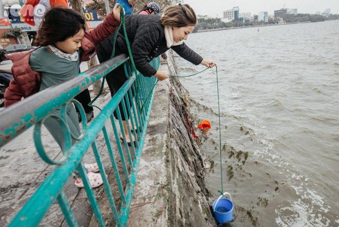 """<p> """"Cách thả cá bằng xô nhựa xuống khá hay, làm như vậy cá chép xuống nước an toàn hơn tránh bị va đập vào thành đá, chị Đinh Thị Hạnh (Hoàng Hoa Thám, Hà Nội) cho biết.</p>"""