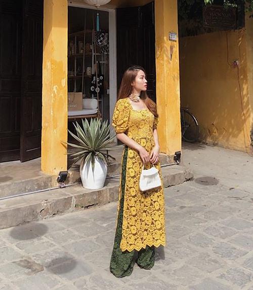 Yến Trang cho thấy độ sành mốt khi kết hợp những xu hướng hot nhất trong một chiếc áo dài: tay bồng, cổ vuông cổ điển và chất liệu ren không gò bó.