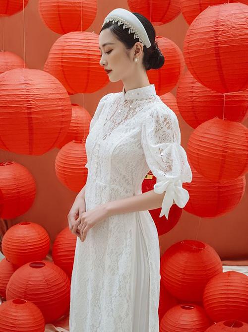Jun Vũ mặc áo dài trắng nhưng không bị nhàm chán nhờ chất liệu ren cao cấp, đi kèm là phần tay bồng đính nơ xinh xắn.