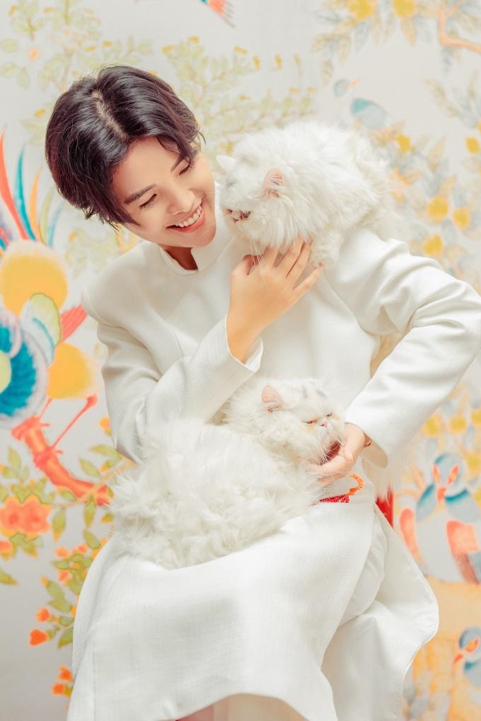 """<p> Đón Tết, nữ ca sĩ thực hiện bộ ảnh tặng fan cùng hai chú mèo cưng có tên Ốp La và Bánh Mì. Trong trang phục áo dài cách tân, nữ ca sĩ có những khoảnh khắc vui vẻ bên hai """"người bạn"""". Đây cũng là lần đầu tiên hai chú mèo cưng của nữ ca sĩ được cho """"lên sóng"""".</p>"""