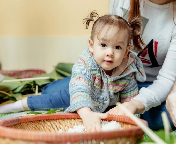 <p> Bé Lina không hề quấy phá, thậm chí còn giúp mẹ nhặt nguyên liệu gói bánh.</p>
