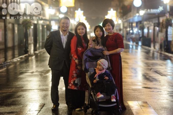 <p> Một gia đình bất chấp chấp cơn mưa ngày càng nặng hạt, dạo phố phường đêm giao thừa.</p>