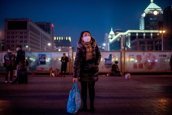<p> Một người phụ nữ đeo khẩu trang đợi ngoài ga tàu ở Bắc Kinh. Ảnh:<em> AFP.</em></p>