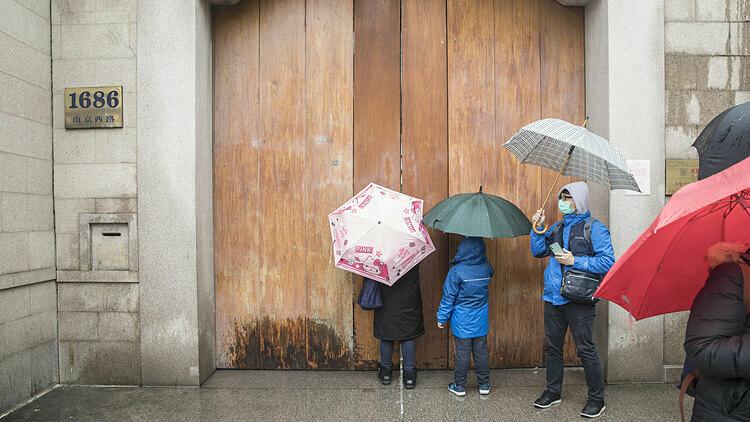 Du khách đứng bên ngoài một ngôi đền đóng cửa ở Thượng Hải, Trung Quốc hôm 25/1. Ảnh: Bloomberg.
