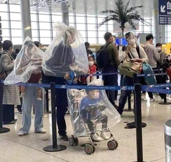 Một gia đình bốn người đã nghĩ ra cách trùm bao nilon to vào người trong lúc xếp hàng chờ làm thủ tục ở sân bay, nhằm tránh tiếp xúc ở cự ly gần với bất cứ ai có thể là nguồn lây nhiễm.