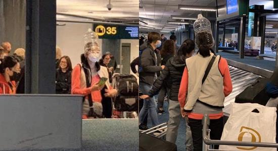 Du khách đội chai nhựa lên đầu kèm khẩu trang khi đứng ở khu vực xác nhận hành lý ở sân bay Vancouver, Canada.