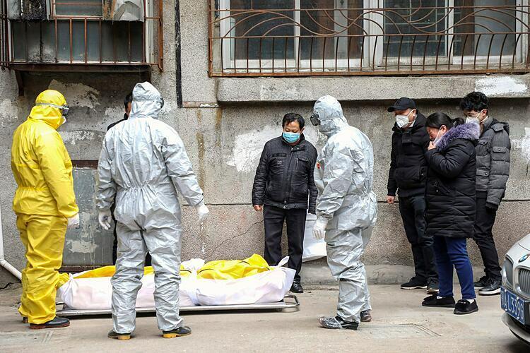 Nhân viên nhà tang lễ mang đi thi thể một người chết trong một ngôi nhà ở Vũ Hán. Ảnh: AP