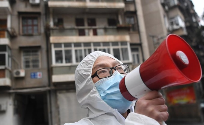 <p> Một nhân viên y tế thành phố Vũ Hán dùng loa phóng thanh để thông báo hoạt động kiểm tra sức khỏe trước khi đoàn công tác vào chung cư.</p>