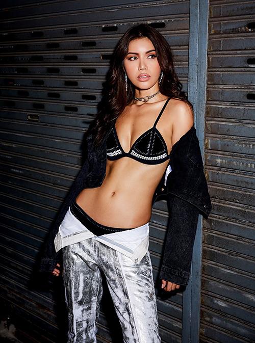 Minh Tú mặc bikini và quần buông khuy khoe thân hình săn chắc, dù vậy bối cảnh trong một khu chợ lại có phần không phù hợp.