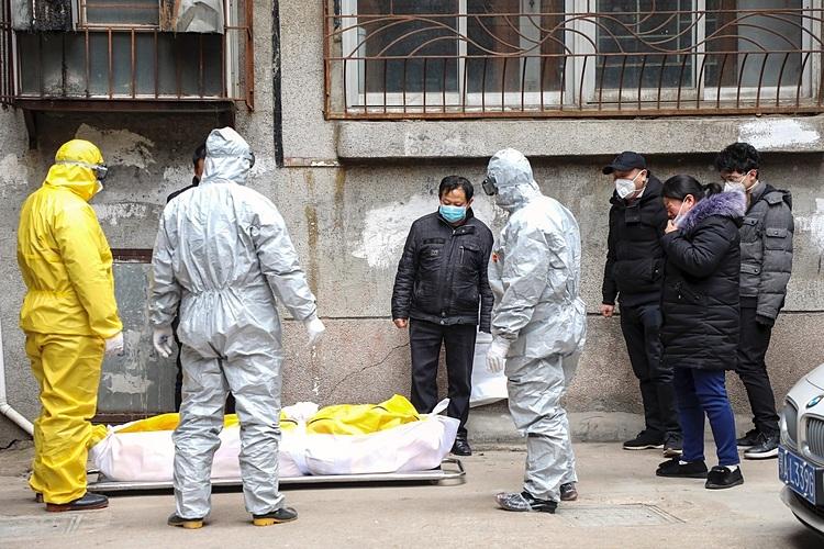 Nhân viên nhà tang lễ mang đi thi thể một người chết trong một ngôi nhà ở Vũ Hán. Ảnh: AP.