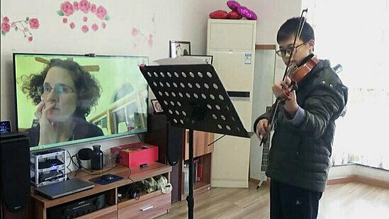 Cậu bé Yunhe Tang học đàn với cô giáo qua video.
