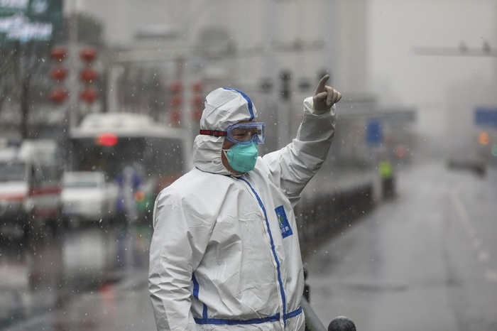 Nhân viên địa phương chỉ đạo các phương tiện giao thông đến bệnh viện để điều trị bệnh nhân nCoV tại Vũ Hán. Ảnh: AP