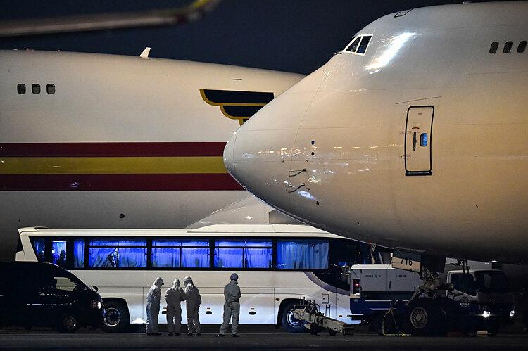 Xe bus chở hành khách Mỹ đến sân bay Haneda, Tokyo sau khi rời cảng Yokohama. Ảnh: AFP.