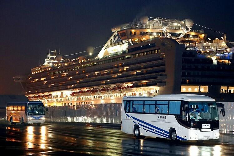 Xe buýt chở hành khách Mỹ rời cảng Yokohama vào 17/2. Ảnh: Kyodo.