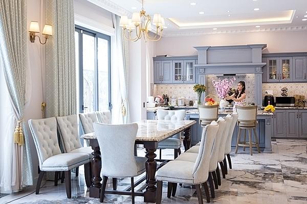 Cơ ngơi của vợ chồng Đăng Khôi được xây theo lối cổ điển. Phòng khách bày nhiều ghế, nối liền với gian bếp. Căn nhà sử dụng nhiều cửa kính, đón ánh sáng tự nhiên.
