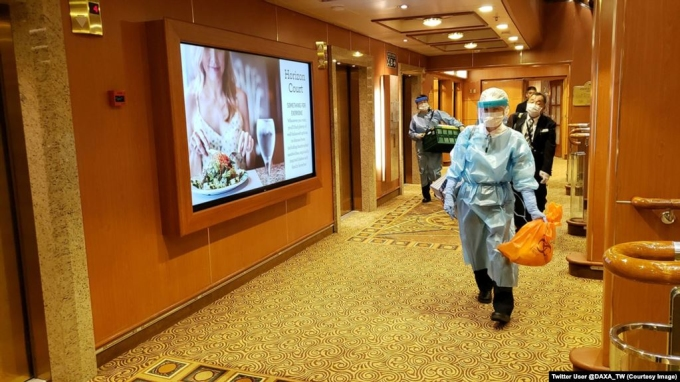 <p> Nhân viên y tế trong bộ đồ bảo hộ trên tàu du lịch Diamond Princess. Ảnh: <em>AP.</em></p>