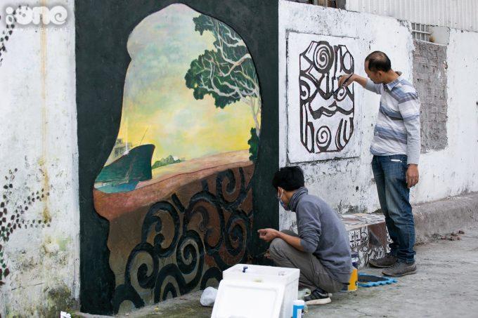 """<p> Các họa sĩ đang hoàn thành những khâu cuối cùng trên tác phẩm """"Bức tường danh vọng"""".</p>"""