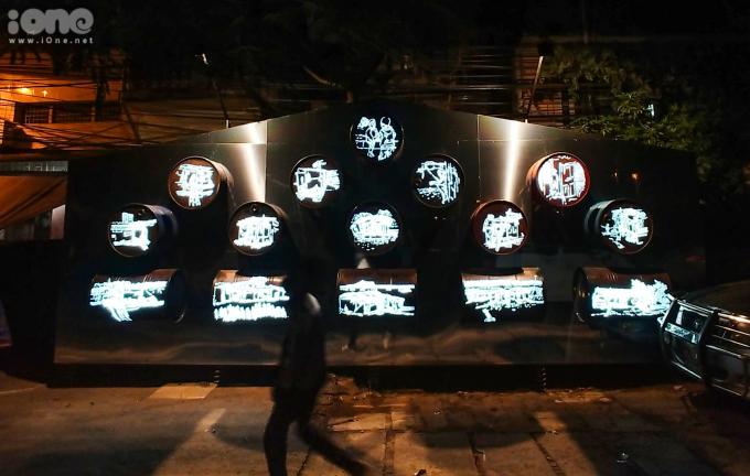"""<p> Hiệu ứng ánh sáng ban đêm trên tác phẩm """"Nhà nổi"""" của họa sĩ Lê Đăng Ninh. Tác phẩm này sử dụng các thùng phuy bỏ đi - vật liệu không thể thiếu của những ngôi nhà nổi trên sông Hồng.</p>"""