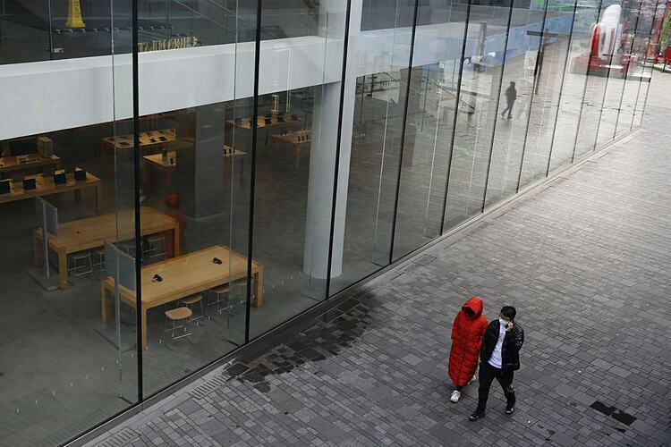 Mọi người đi ngang qua một cửa hàng Apple đã đóng cửa ở Bắc Kinh, Trung Quốc, hồi đầu tháng này. Ảnh: EPA.
