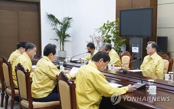 Tổng thống Hàn Moon Jae In nghe báo cáo tại cuộc khẩnsáng 21/2, với sự tham gia của Thủ tướng Chung Sye Kyun, bộ trưởng Bộ Y tế và Phúc lợi và bộ trưởng bộ Hành chính và An ninh. Ảnh: Yonhap News.
