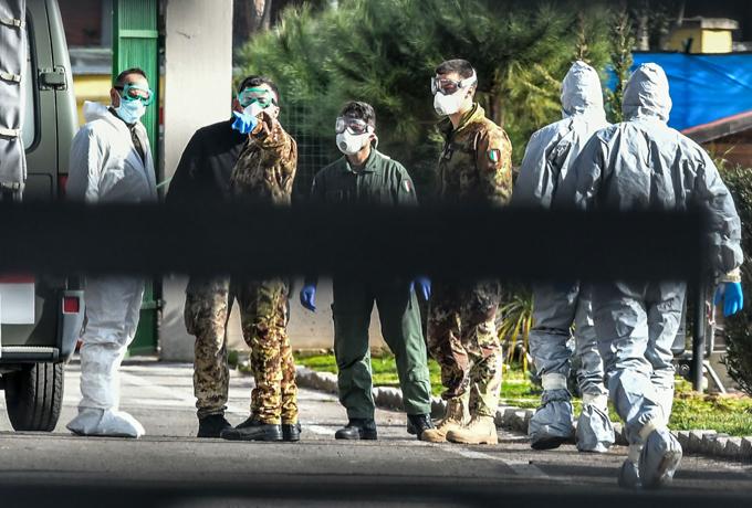 Các quân nhân Italy mặc đồ bảo hộ đứng ở trung tâm kiểm dịch phía Nam của Rome. Ảnh: AFP.