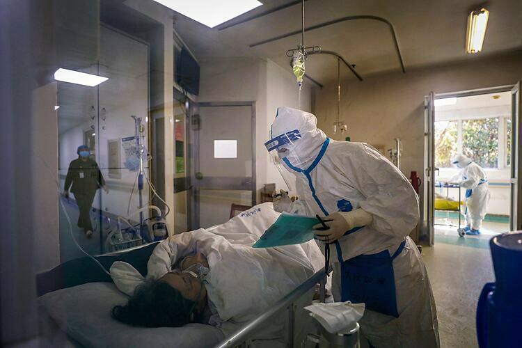 Một nhân viên y tế chăm sóc cho bệnh nhân nhiễm virus corona ở bệnh viện thuộc Vũ Hán. Ảnh: AP.