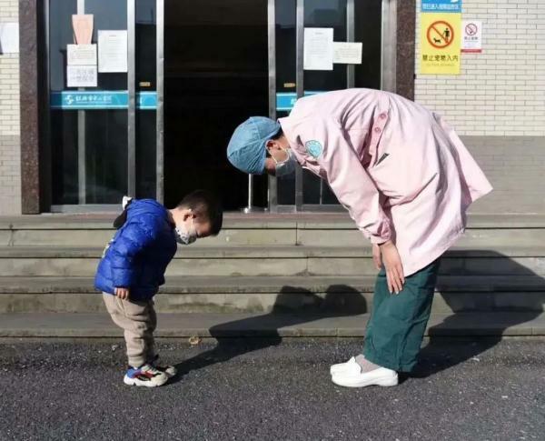 Em bé 3 tuổi cúi đầu cảm ơn bác sĩ khi được xuất viện. Ảnh: Xinhua.