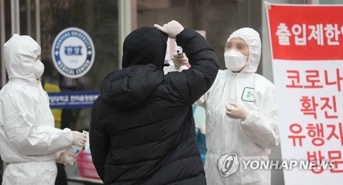 Nhân viên y tế kiểm tra thân nhiệt tại  trước cửa Bệnh viện Đại học Hanyang, Sangnam-dong, Nam Gyeongsang. Ảnh: Yonhap.