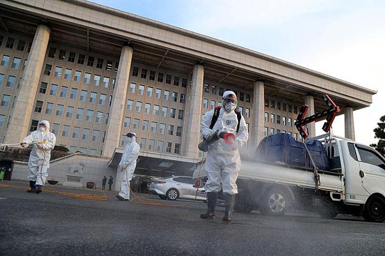 Hàn Quốc phun thuốc khử trùng bên ngoài tòa nhà Quốc hội hôm 24/2. Ảnh: Reuters.