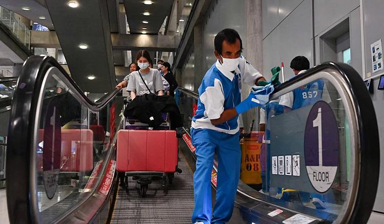 Nhân viên khử trùng tay vịn thang cuốn ở sân bay Suvarnabhumi, Bangkok. Ảnh: AFP.