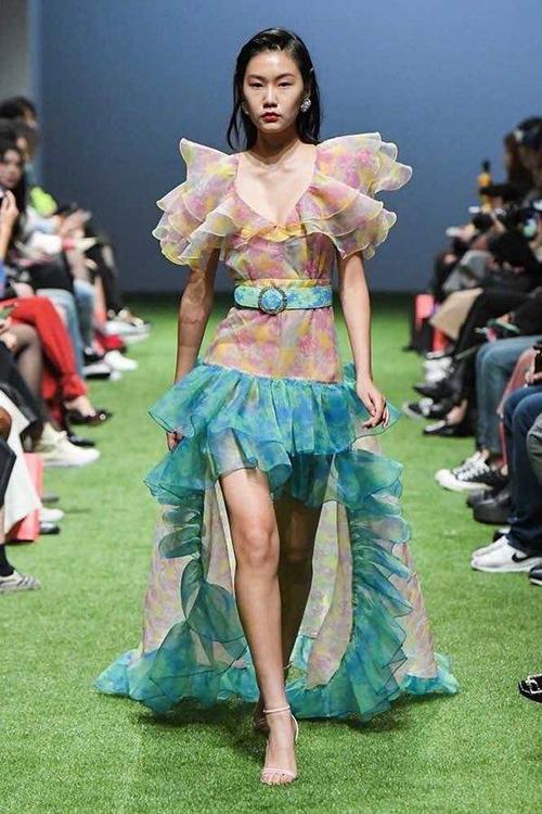 Đây là một thiết kế của thương hiệu Hàn Quốc Langnlu, đã được giới thiệu trên sàn diễn Seoul Fashion Week mùa Xuân Hè 2020. Trang phục có màu sắc, họa tiết hoa lá, kiểu dáng nhiều diềm bèo.