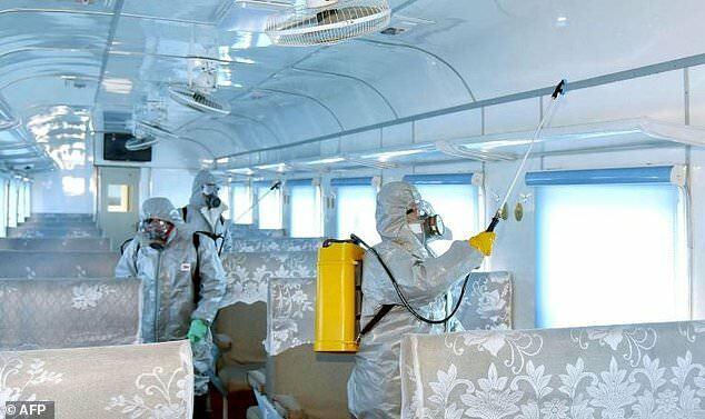 Công nhân mặc đồ bảo hộ phun thuốc khử trùng tại một chuyến xe ở Triều Tiên. Ảnh: AFP.