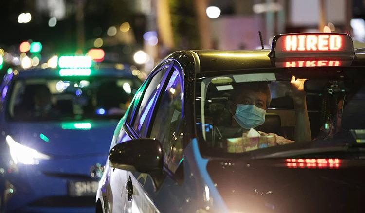 Tài xế taxi đeo mặt nạ chờ đèn giao thông ở khu vực trung tâm thương mại Singapore. Ảnh: EPA.