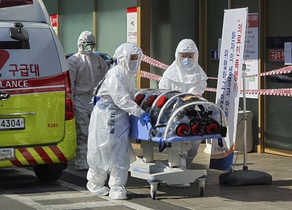 Nhân viên y tế di chuyển một bệnh nhân nghi nhiễm bệnh ở Daegu. Ảnh: AP.