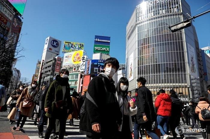 Người đi bộđeo khẩu trang tại một con phố ở Shibuya (Tokyo) ngày 24/2. Ảnh: Reuters.