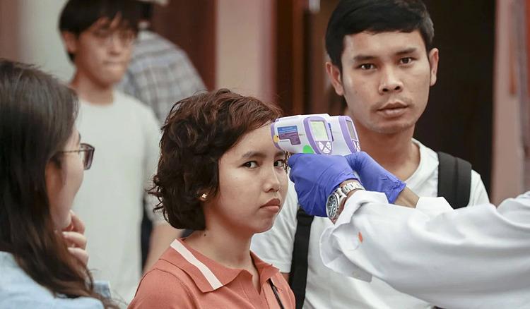 Một người phụ nữ kiểm tra thân nhiệt ở khu phố Tàu, tại Singapore ngày 17/2. Ảnh: EPA.