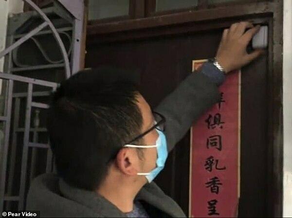 Một nhân nhân viên cộng đồng đang cài đặt thiết bị trên cánh cửa ở Ninh Ba, tỉnh Chiết Giang, Trung Quốc.