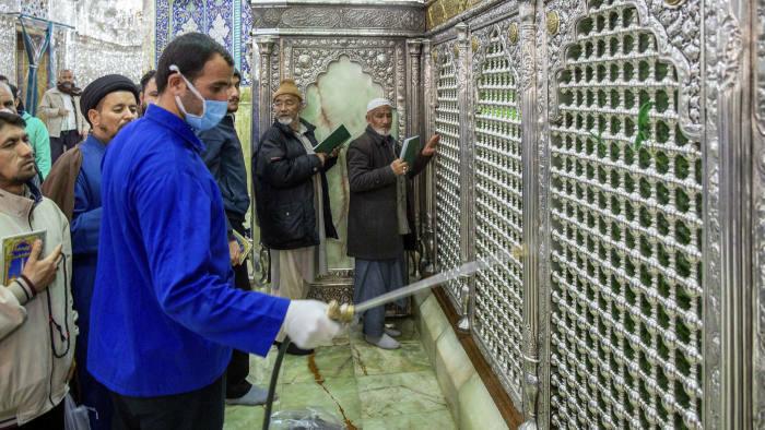 Một người đàn ông khử trùng một ngôi đền Hồi giáo ở thành phố Qom, Iran. Ảnh: AP.