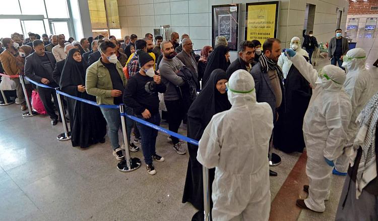 Đội ngũ y tế kiểm tra thân nhiệt hành khách Iraq trở về từ Iran tại sân bay quốc tế Najaf, ngày 21/2. Ảnh: AFP.